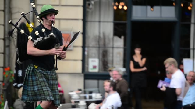 mid shot, a street performer is simultaneously riding a unicycle, playing bagpipes and juggling swords. street entertainers perform on edinburgh's... - kilt stock videos & royalty-free footage