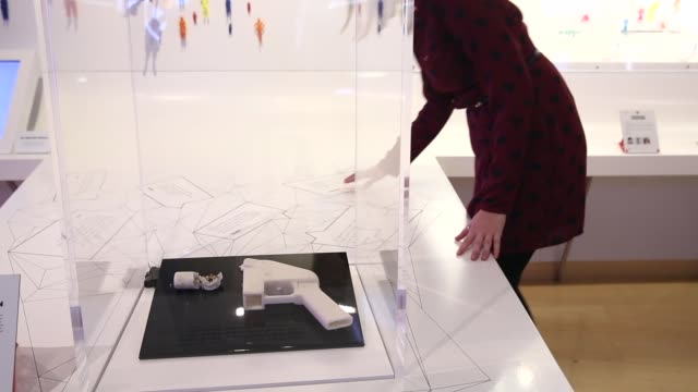 mid shot a woman admires a 3d printed handgun which was created and fired by finnish journalist ville vaarne and which is displayed in the exhibition... - gun stock videos & royalty-free footage