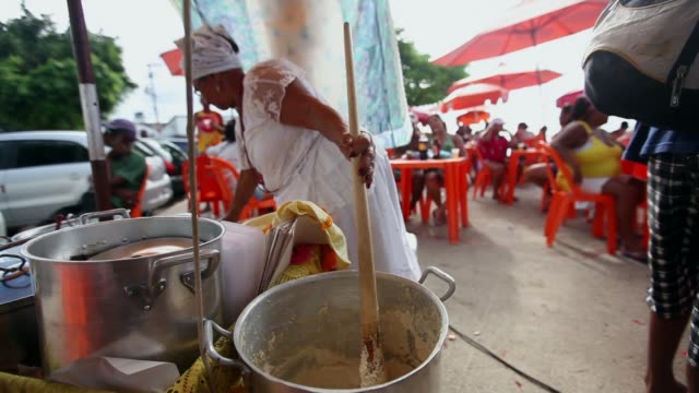 mid shot, a woman makes traditional bahian food the beach on january 12, 2014 in salvador, brazil. - ゴールを狙う点の映像素材/bロール