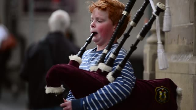 mid shot, a young boy playing bagpipes. street entertainers perform on edinburgh's royal mile during the city's festival fringe on august 21, 2013 in... - jonglieren stock-videos und b-roll-filmmaterial