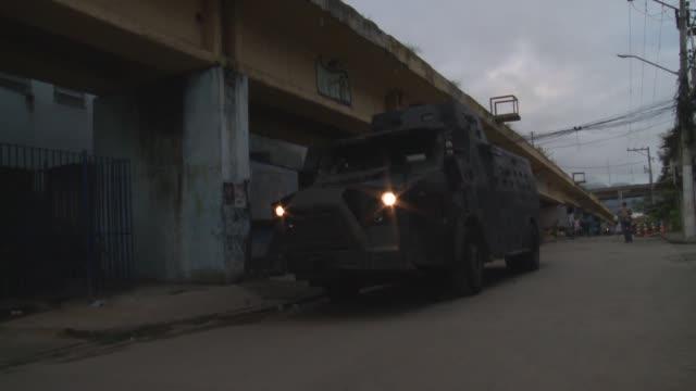 mid shot bope armoured car enters caju early morning - 陸軍点の映像素材/bロール