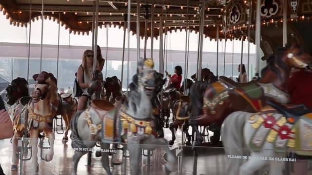 Mid Shot children riding the carousel Janes Carousel is a classic 3row machine with 48 exquisitely carved horses and two superb chariots It was...