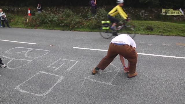 mid shot fans of bradley wiggins sketch a bicycle and write a message on the tarmac in support of their cycling idol stage six of the tour of britain... - tour of britain stock videos & royalty-free footage