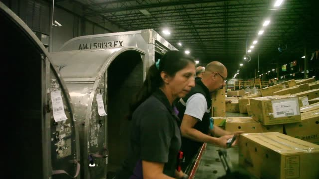 Mid Shot FedEx employees sort through packages at a shipping center as they are heading out for delivery on Cyber Monday on December 2 2013 in Miami...