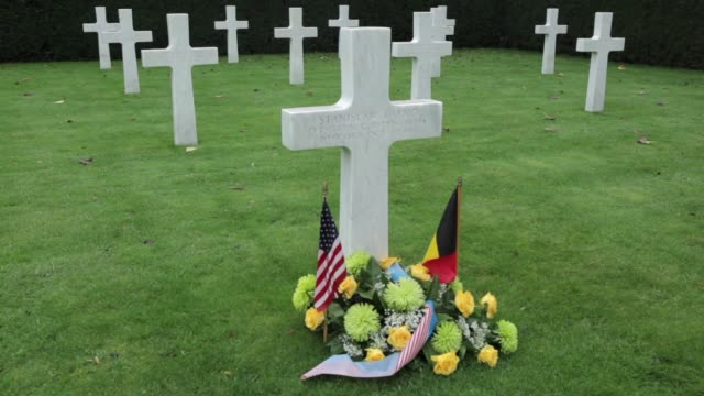 mid shot gravestone flowers and flags on the grave of private stanislaw labno from nebraska at the cemetery in flanders where americans who died in... - gravestone stock videos & royalty-free footage