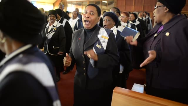 mid shot members of the congregation sing during a sunday service at regina mundi church in soweto on june 16 2013 in johannesburg south africa youth... - 礼拝点の映像素材/bロール
