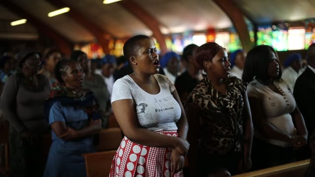 mid shot members of the congregation sing during sunday service on a national day of prayer for nelson mandela at regina mundi church in soweto on... - religious service stock videos and b-roll footage