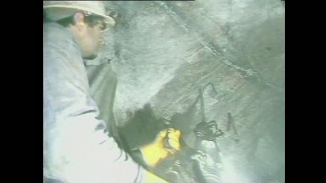 vídeos de stock e filmes b-roll de mid shot miner using machinery to break rock underground at the wheal jane tin mine in cornwall, uk; 1986. - hitting