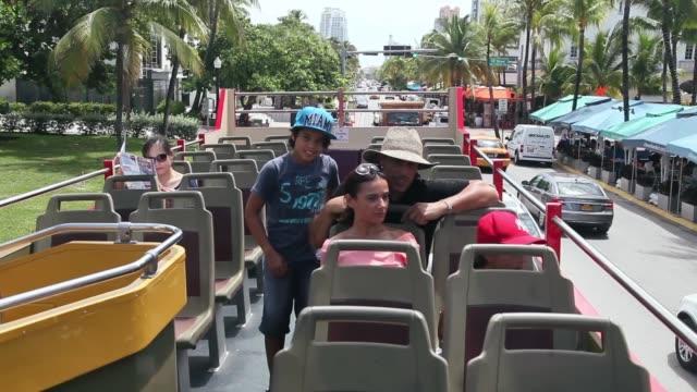 Mid Shot Mustafa Bachiri and his wife Laetitia Bachiri enjoy their family vacation onboard a Big Bus Tour double decker bus during a sightseeing trip...