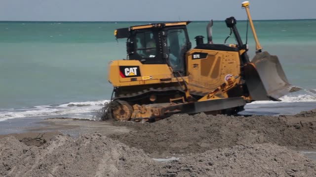 Mid shot of a bulldozer pushing sand at the beach A bulldozer is used to push sand from a discharge pipe into place during a federally funded shore...
