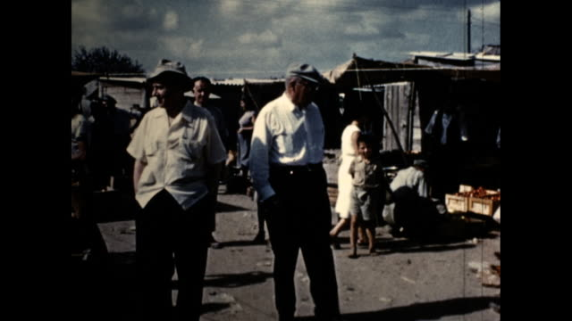 mid shot of a buzzing village in israel during the 1950's. a white man is interacting with vendors who are getting their produce ready for sale at... - buzzing stock videos & royalty-free footage