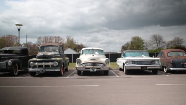 mid shot of a classic american car passing by. fans of rock and roll, rockabilly, rockin' blues and americana gather at seacroft holiday camp in... - holiday camp stock videos & royalty-free footage