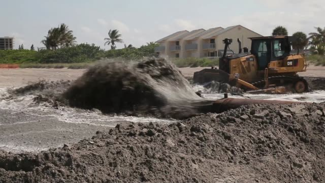 vídeos de stock, filmes e b-roll de mid shot of a discharge pipe pumping water onto the beach a bulldozer is used to push sand from a discharge pipe into place during a federally funded... - erodido
