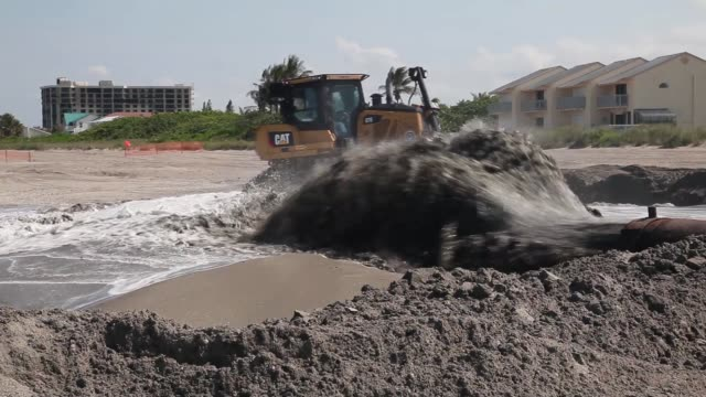 Mid shot of a discharge pipe pumping water onto the beach A bulldozer is used to push sand from a discharge pipe into place during a federally funded...