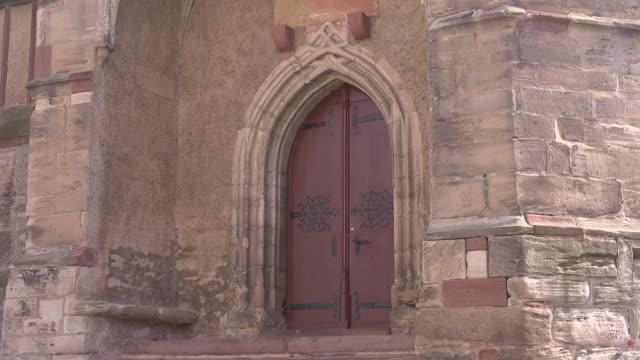 mid shot of a door of the church st. george in mansfeld - 宗教的指導者 マルティン・ルター点の映像素材/bロール
