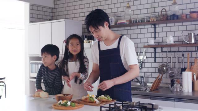 vídeos y material grabado en eventos de stock de medio trago de un padre enseñando a sus dos hijos a cocinar - padre soltero