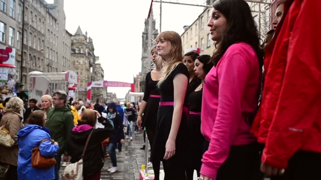 mid shot of a female choir performing on the royal mile street entertainers perform on edinburgh's royal mile during the city's festival fringe on... - マイル点の映像素材/bロール