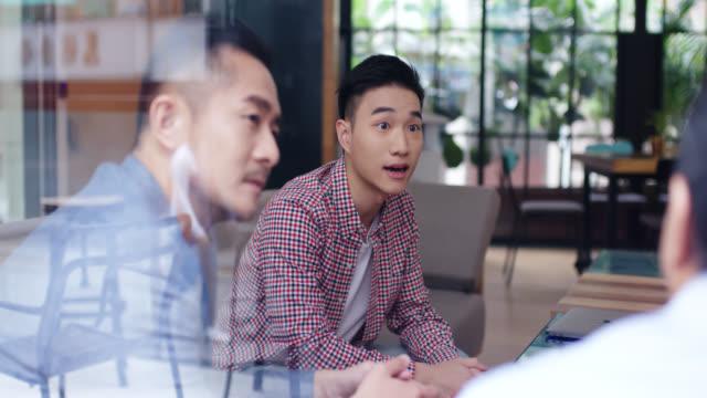 vídeos de stock e filmes b-roll de mid shot of a group of office workers having an informal meeting through a window - cultura da ásia oriental