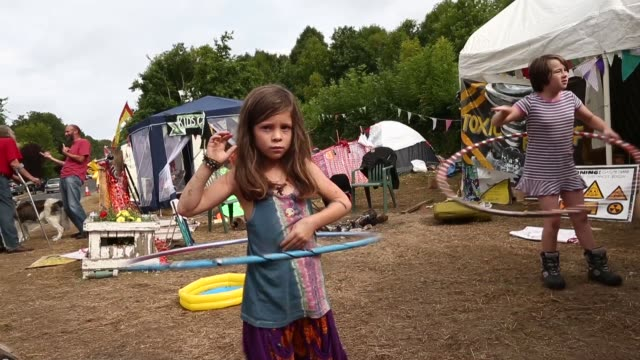 mid shot of a little girl playing hula hoop at the protestors' camp. protesters gather outside a drill site operated by cuadrilla resources ltd on... - west sussex stock videos & royalty-free footage