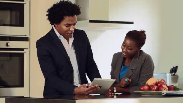 mid shot of a man and a woman using an ipad - formelle geschäftskleidung stock-videos und b-roll-filmmaterial