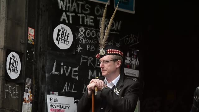 mid shot of a man dressed in traditional scottish clothing. street entertainers perform on edinburgh's royal mile during the city's festival fringe... - kilt stock videos & royalty-free footage