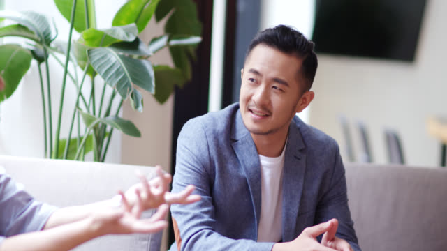 mid shot of a man in a busy design office having an informal meeting - chinese ethnicity stock videos & royalty-free footage