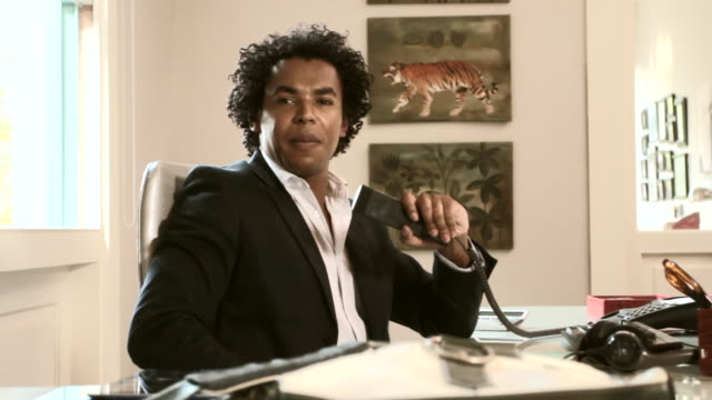 mid shot of a man sitting at a desk and speaking on a telephone - formal businesswear stock videos & royalty-free footage