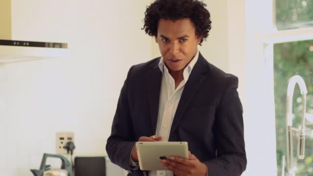 mid shot of a man using an ipad - formelle geschäftskleidung stock-videos und b-roll-filmmaterial