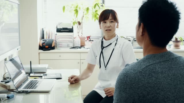 mid shot of a mature female doctor consulting with a mid adult man at a hospital - solo giapponesi video stock e b–roll