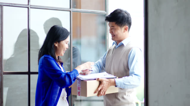 mid shot of a mature woman signing for a package from the deliveryman - delivery person stock videos & royalty-free footage
