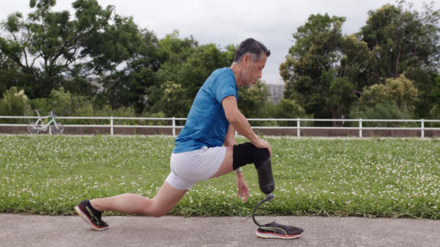vídeos de stock, filmes e b-roll de tiro meados de um corredor sênior do amputado que estica - atleta