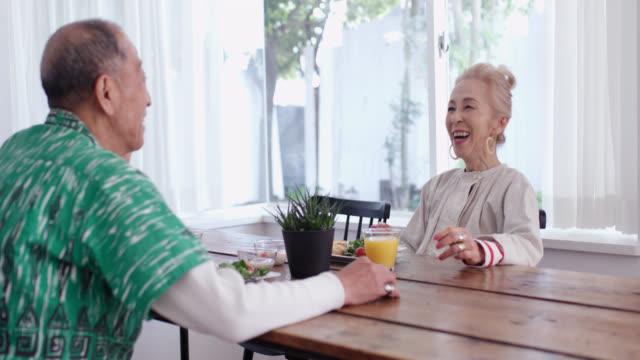 一緒に朝食を楽しむシニアカップルのミッドショット - リタイアメント点の映像素材/bロール