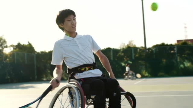 テニスをしている車椅子の10代の少年のslo moミッドショット - テニス点の映像素材/bロール