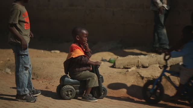 mid shot of a young boy on a toy bike residents of diepsloot township go about their daily activities as they pass the public holiday following youth... - soweto stock videos & royalty-free footage