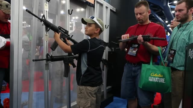 Mid shot of a young boy practice aiming with a assault rifle during the 2013 NRA Annual Meeting and Exhibits at the George R Brown Convention Center...
