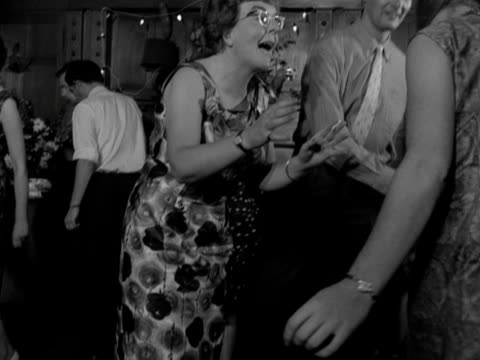 Mid shot of a young couple and an older woman dancing the