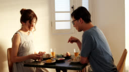 Mid shot of a young couple eating Japanese rice balls together at home