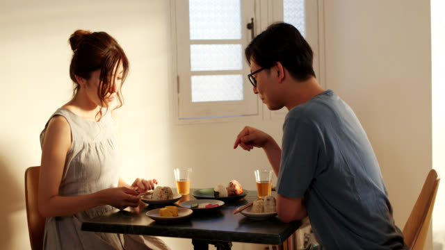 mid shot of a young couple eating japanese rice balls together at home - married stock videos & royalty-free footage