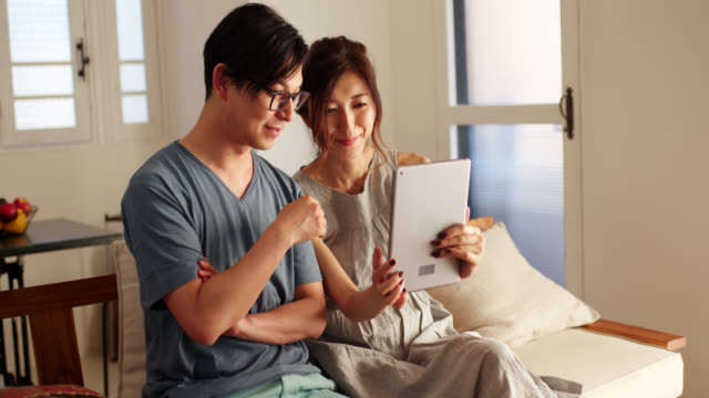 mid shot of a young couple looking at a digital tablet in the living room - married stock videos & royalty-free footage