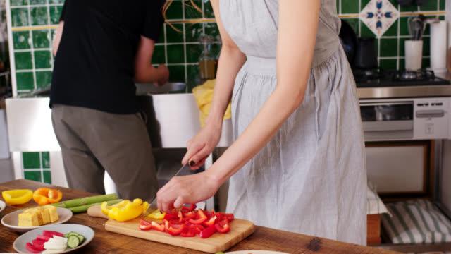 夕食を準備するために台所で一緒に働く若いカップルのミッドショット - kitchen点の映像素材/bロール