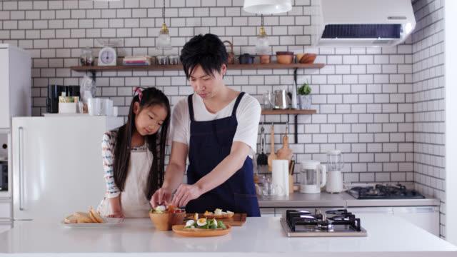 家庭で一緒に調理する若い父親と娘のミッドショット - daughter点の映像素材/bロール
