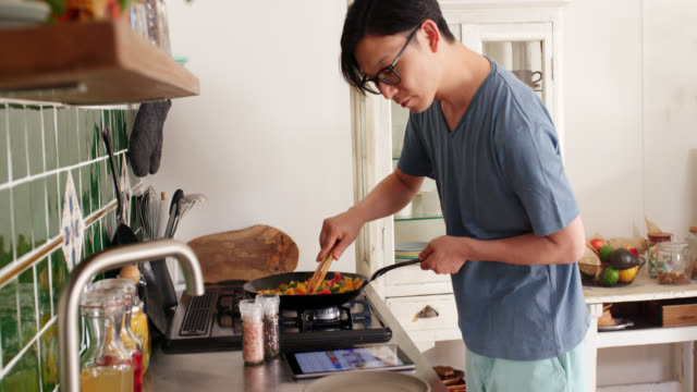 mid shot of a young man checking a digital tablet and cooking dinner at home - cooking stock videos & royalty-free footage