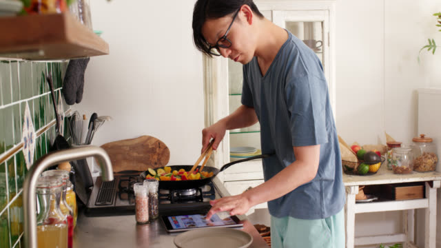 mid shot of a young man checking a digital tablet and cooking dinner at home - content stock videos & royalty-free footage
