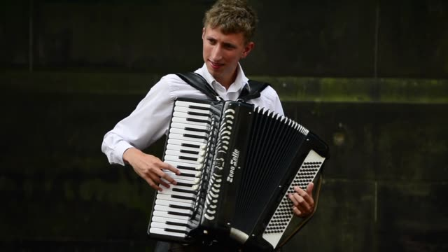 vídeos y material grabado en eventos de stock de mid shot of a young man playing the accordion street entertainers perform on edinburgh's royal mile during the city's festival fringe on august 21... - acordeonista