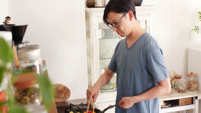 mid shot of a young man preparing dinner at home - meal preparation stock videos & royalty-free footage
