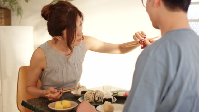 mid shot of a young woman showing her boyfriend how to properly use chopsticks - rice ball stock videos & royalty-free footage