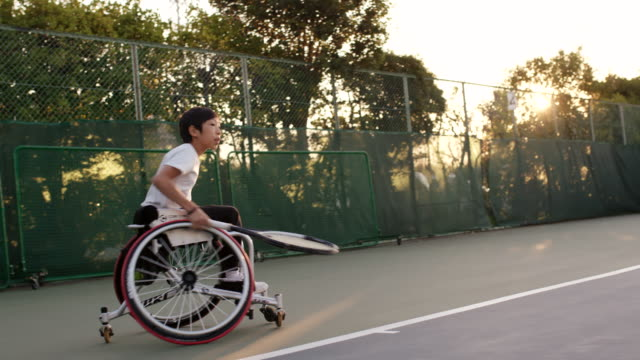 slo mo mid shot of an adaptive tennis player practicing - paralysis stock videos & royalty-free footage