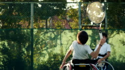 SLO MO mid shot of an adaptive tennis player serving