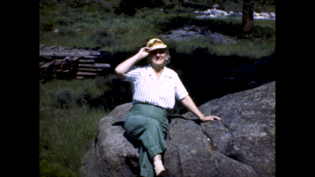 mid shot of an older woman posing on large rock in the country side as she puts on a hat. - boulder rock stock-videos und b-roll-filmmaterial