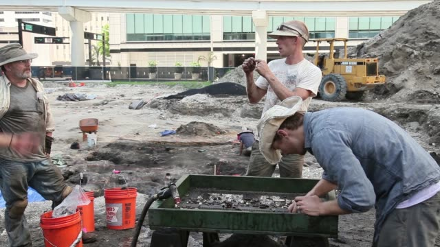 Mid shot of archeologists sifting mud in search for artifacts Archaeologists with the Archaeological and Historical Conservancy work on excavating a...